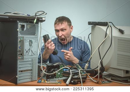 Overloaded enraged computer technician engineer swears into the phone. Computer repairman. PC repair service center.