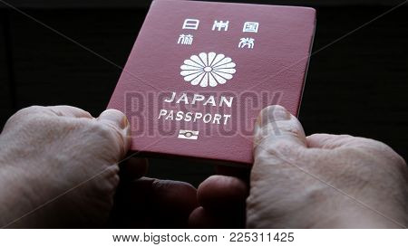 Persons hand holding and giving passport of Japan