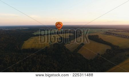 Aerial view Hot air balloon in the sky over a field in the countryside in the beautiful sky and sunset. Balloon silhouette with sunrise, Aerostat fly in the countryside.