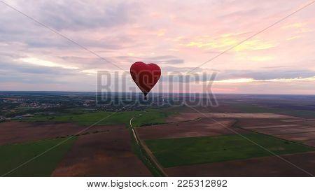 Hot air balloon shape of a heart in the blue sky. Aerostat, Airship. Red balloon.