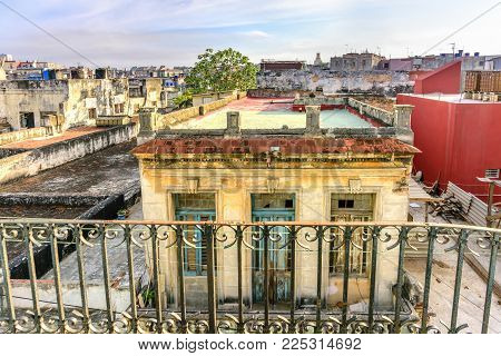 View from the balcony on the roofs of old, dilapidated, flaky buildings and a gray-blue sky in the slums area in Havana in Cuba