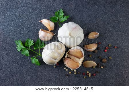 Garlic. Fresh Garlic.  Head and cloves of garlic with parsley  and pepper. Food background.