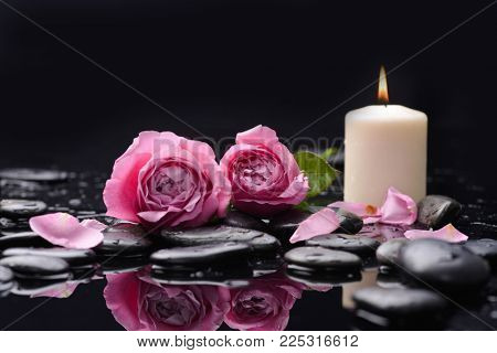 two pink rose petals with candle and therapy stones