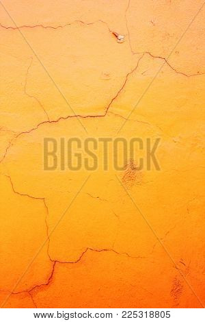 Grunge background with old stucco wall texture with cracked paint of orange color