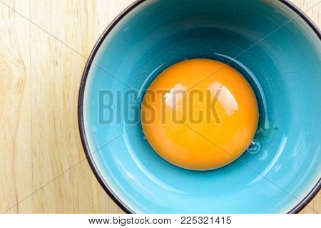 Close up egg yolk in bowl on wooden table, top view