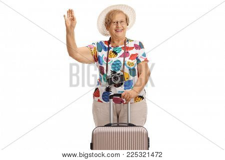 Elderly female tourist with a suitcase waving at the camera and smiling isolated on white background