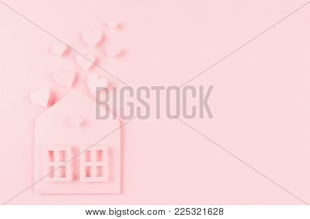 Paper house with fly out red hearts on soft pink color background. Copy space. Valentine day concept for design.