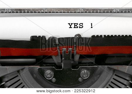 big Text YES written with the old typewriter on white sheet
