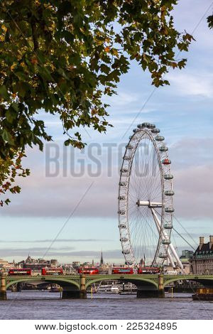 LONDON, UK - OCTOBER 29, 2012: Double decker buses move along the Westminster Bridge over the River Thames, Iconic London Eye giant observation wheel is seen in background