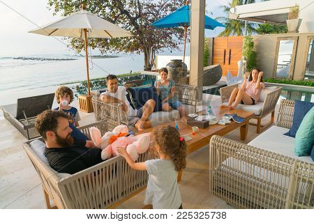 KOH SAMUI, THAILAND - JANUARY 21, 2018; Holidaying modern young families sitting around outside enjoying one and others company in warm tropical late sun in beachside environment.