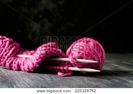 closeup of a pink knit cap in knitting progress, next to a ball of yarn and a pair of  needles, on a rustic wooden table against a dark background with some blank space on top