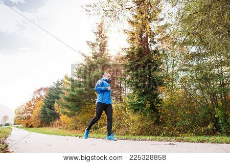 Young athlete in blue jacket running outside in colorful sunny autumn nature. Trail runner training for cross country running.