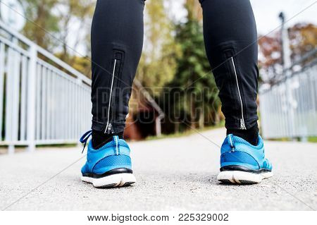 Legs of young runner standing on an asphalt path. Unrecognizable trail runner training for cross country running. Rear view.