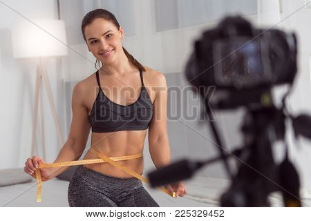 Being slim. Beautiful vigorous athletic young woman holding a waist tape measure and smiling while making a video for her blog