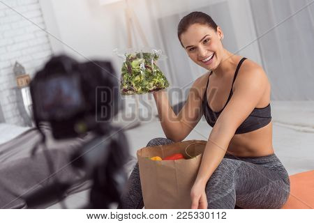 Fresh vegetables. Pretty exuberant well-built young woman smiling and having a packet with vegetables and showing greenery while making a video for her blog
