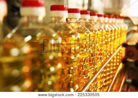 line or conveyor for food production of sunflower oil. Bottles with vegetable oil close-up against the background of factory equipment