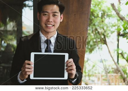 Businessman Hold Digital Tablet At Workplace. Young Man Shows Information In Touchpad Outdoors. Free