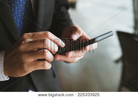 Businessman Holding Smartphone & Using App. Man Texting Message Outdoors. Social Network Communicati