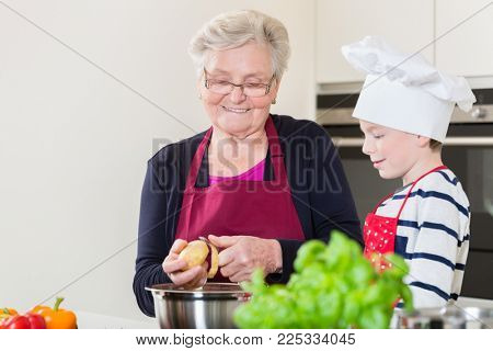 Happy grandma and grandson cooking together