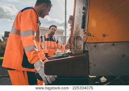 Garbage removal men working for a public utility emptying trash container