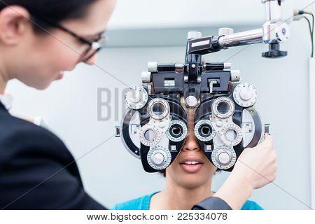 Optometrist and woman at eye examination with phoropter