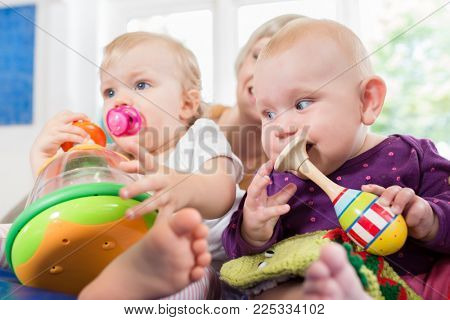 Infants with pacifier in toddler group playing with toys