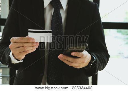Man Holding A Credit Card And Using Smart Phone For Online Shopping At Cafe. Businessman Purchase Go