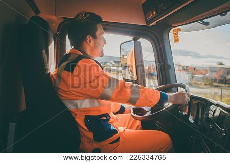 Garbage removal worker driving a waste truck