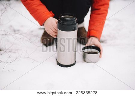 Woman Hands Pours Hot Tea Or Coffee Out Of Thermos On Winter Forest Background.
