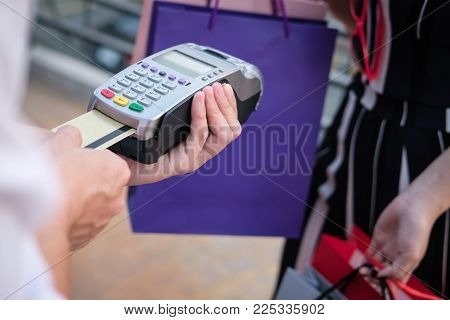 Woman Make Payment With Credit Card Swipe Through Terminal. Customer Paying With Edc Or Swiping Mach