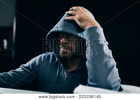 a male hacker is sitting in a dark room at the table