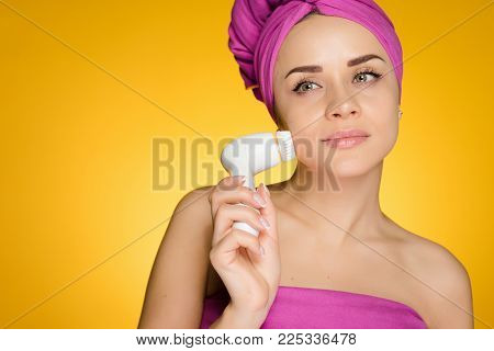 woman with a towel on her head after showering her face with a brush for deep face cleansing