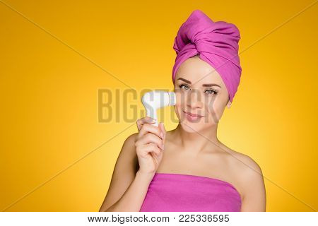 woman with a towel on her head brush her face with a brush for deep cleansing of the skin of her face