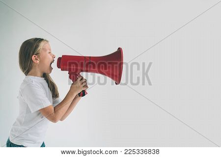 Portrait of young girl shouting using megaphone over background Chil in white shirt, studio shot.
