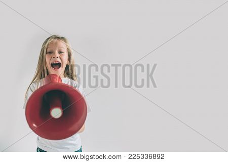 Portrait of young girl shouting using megaphone over background Chil in white shirt, studio shot .