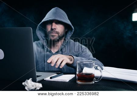 male hacker in a sweatshirt with a hood sitting at a table and drinking tea
