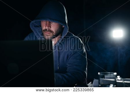 male hacker in a sweatshirt with a hood sitting at a table and looking at a laptop in a dark room