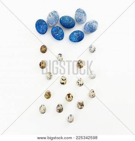 Blue Speckled Easter Egg with quail eggs on white background. Flat lay. Top view. Creative concept