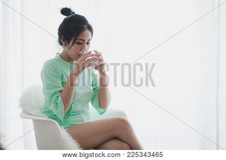 Lifestyle Scene Of Young Asian Woman Drinking Coffee While Reading Book In Morning Time. Weekend Act