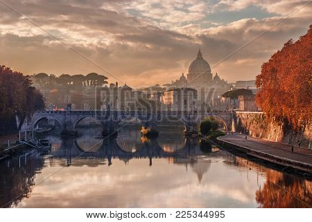 Autumn sunset over River Tiber with Saint Angel Bridge and Saint Peter Dome in the evening haze