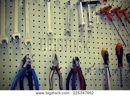 Repair Tools Hung On The Wall Of A Mechanical Workshop With Vintage Style Effect