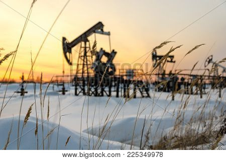 Blurred pump jack, wellhead and pipeline during sunset in the oilfield. Winter period. Oil and gas concept. Grass foreground.