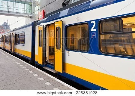 Amsterdam, Netherland - June 25, 2017: Yellow Dutch Train On The Amsterdam Centraal Station Platform
