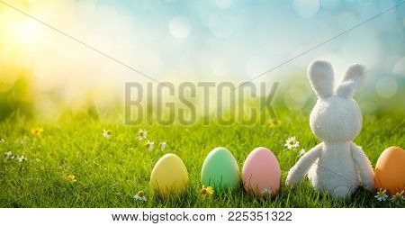 Sugar rabbit with easter eggs on meadow grass