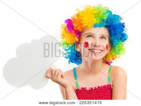 Lively little girl in bright colouful clown wig holding white speech bubble isolated on white background