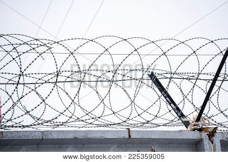 Barbed wire on concrete fence on the background of the grey sky