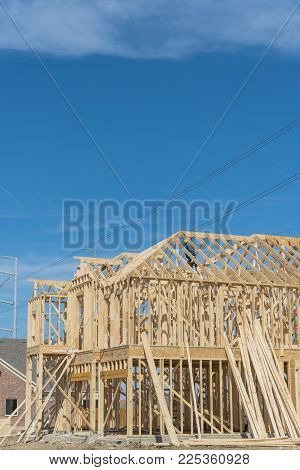 Wood frame house under construction with builder roofing. New two-story stick built next to completed homes in Irving, Texas, USA. Joist, timber frame panels and temporary struts. Electrical wires