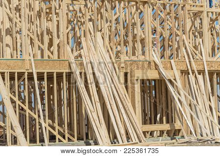 Close-up wooden frame house under construction in Irving, Texas, USA. Upper structure rest on wide joists with floor platform framing of frame panels and temporary struts. Two-story stick built home