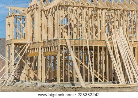 Close-up wood frame house under construction next to completed homes in Irving, Texas, USA. New two-story stick built, joist and timber frame panels with temporary struts, electrical wires.