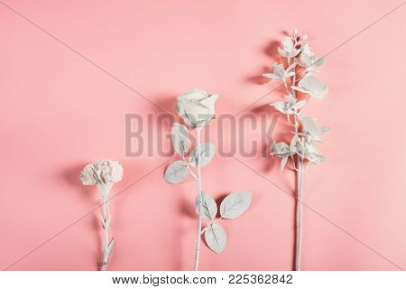 Three white flowers on a pink background in a minimal composition. Purity symbol.
